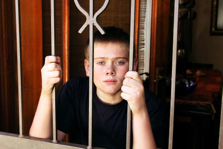 Unhappy Young Boy Locked Behind Security Gate Inside House for Protection Stock Photo - 15707284