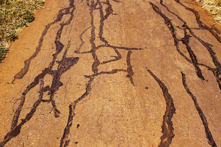 breaking up: Rural Road Surface Cracks and Breaking Up Stock Photo