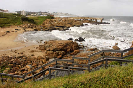 kwazulu natal: Picture of Coastal Town with Wooden Steps and Concrete Jetty in Storm