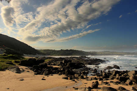 kwazulu natal: Picture of Black Rocks and White Cloads in Blue Sky at Beach Stock Photo