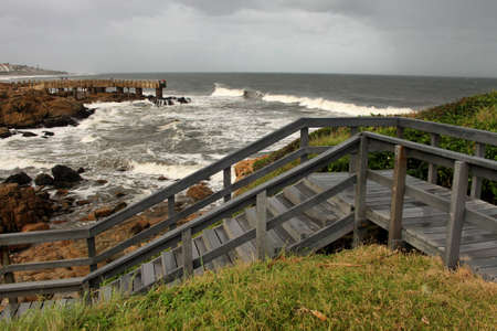 kwazulu natal: Picture of Wooden Steps and Concrete Jetty in Storm over Sea Stock Photo