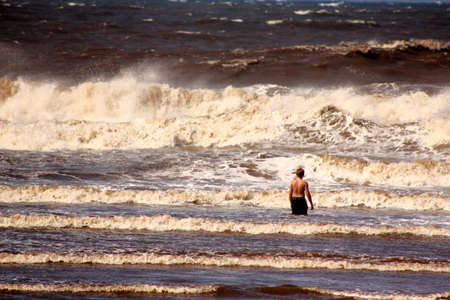 Lone Boy Standing in the Stormy Sea photo