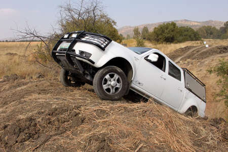 rustenburg: BAFOKENG ? MAY 2013: White Tata 2.2l Dicor going over steep hill obstacle at new 4x4 track opening event May 18, 2013 at Bafokeng, Rustenburg, South Africa   Editorial