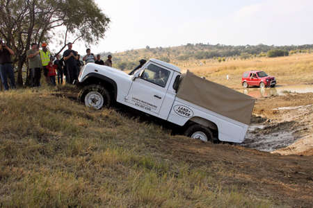 scaling: BAFOKENG ? MAY 2013: White Land Rover Defender 110 HC scaling steep obstacle at new 4x4 track opening event May 18, 2013 at Bafokeng, Rustenburg, South Africa   Editorial