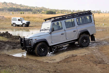 BAFOKENG ? MAY 2013: Silver Land Rover Defender 110 SW going through water obstacle at new 4x4 track opening event May 18, 2013 at Bafokeng, Rustenburg, South Africa