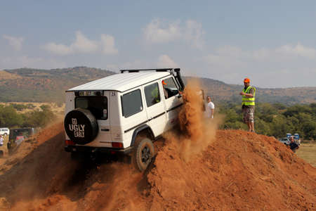 scaling: BAFOKENG ? MAY 2013: White Mercedes-Benz G-Class scaling steep sand hill obstacle at new 4x4 track opening event May 18, 2013 at Bafokeng, Rustenburg, South Africa   Editorial