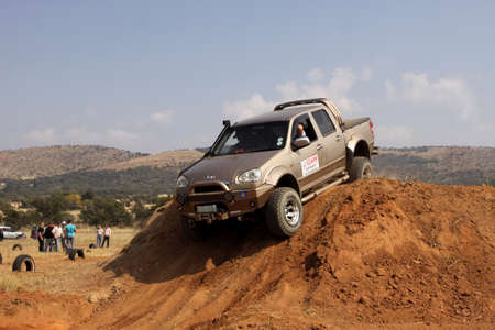 steed: BAFOKENG ? MAY 2013: Gold GWM Steed going over steep sand hill obstacle at new 4x4 track opening event May 18, 2013 at Bafokeng, Rustenburg, South Africa
