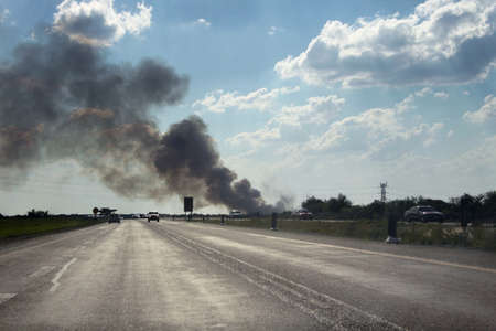 driving conditions: Dangerous Driving Conditions with Smoke Over Freeway