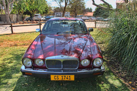 daimler: RUSTENBURG, SOUTH AFRICA - SEPTEMBER 9  A red Daimler Double Six Series III V12 Saloon on display at the half century celebration of the Rusoord old aged home on September 17, 2013 in Rustenburg South Africa     Editorial
