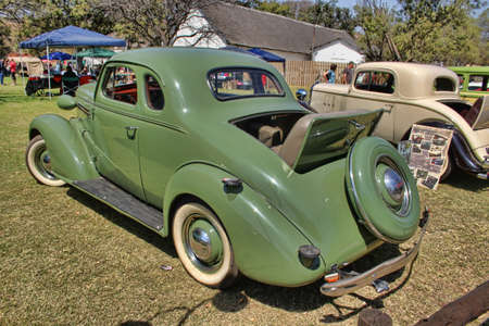 RUSTENBURG, SOUTH AFRICA - SEPTEMBER 9  A green 1936 Ford Two-Door Coupe with Rumble Seat rear side view on display at the half century celebration of the Rusoord old aged home on September 17, 2013 in Rustenburg South Africa