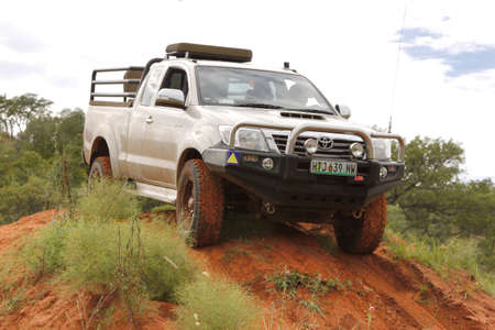 rustenburg: BAFOKENG - MARCH 8: White Toyota Raider Hilux 3.0L crossing obstacle at Leroleng 4x4 track on March 8, 2014 in Bafokeng, Rustenburg, South Africa