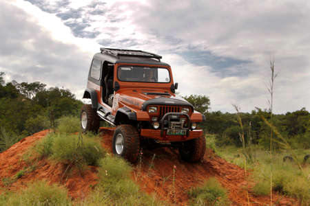 rustenburg: BAFOKENG - MARCH 8: Crush Beige Jeep Wrangler Off-Roader V8 crossing obstacle at Leroleng 4x4 track on March 8, 2014 in Bafokeng, Rustenburg, South Africa Editorial
