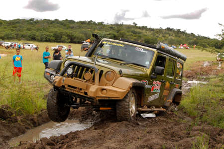 rustenburg: BAFOKENG - MARCH 8: Gecko Pearl Green Jeep Wrangler Rubicon crossing mud obstacle at Leroleng 4x4 track on March 8, 2014 in Bafokeng, Rustenburg, South Africa
