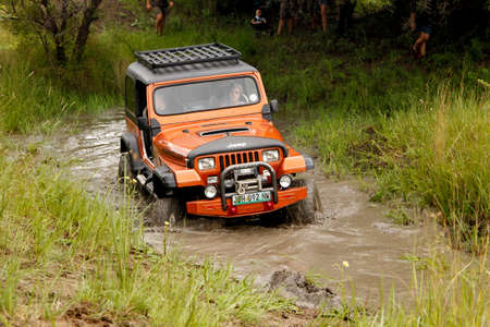 rustenburg: BAFOKENG - MARCH 8: Crush Beige Jeep Wrangler Off-Roader V8 crossing muddy pond obstacle at Leroleng 4x4 track on March 8, 2014 in Bafokeng, Rustenburg, South Africa