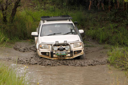 rustenburg: BAFOKENG - MARCH 8: White Mazda BT-50 4x4 3L crossing muddy pond obstacle at Leroleng 4x4 track on March 8, 2014 in Bafokeng, Rustenburg, South Africa