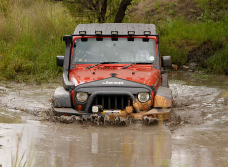 rustenburg: BAFOKENG - MARCH 8 Crush Orange Jeep Rubicon crossing muddy pond obstacle at Leroleng 4x4 track on March 8, 2014 in Bafokeng, Rustenburg, South Africa
