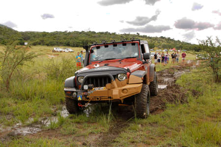 rustenburg: BAFOKENG - MARCH 8: Crush Beige Jeep Rubicon crossing mud obstacle at Leroleng 4x4 track on March 8, 2014 in Bafokeng, Rustenburg, South Africa