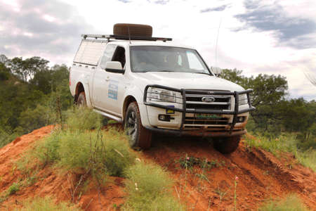 rustenburg: BAFOKENG - MARCH 8: White Ford XLT Supercab 3.0L TDCi with silver canopy crossing obstacle at Leroleng 4x4 track on March 8, 2014 in Bafokeng, Rustenburg, South Africa