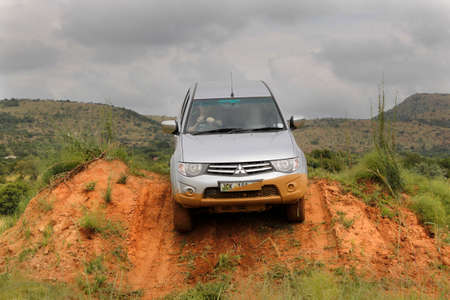 rustenburg: BAFOKENG - MARCH 8: Silver Toyota Triton DHD crossing obstacle at Leroleng 4x4 track on March 8, 2014 in Bafokeng, Rustenburg, South Africa