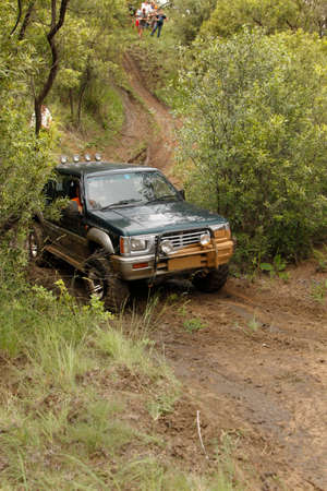 rustenburg: BAFOKENG - MARCH 8: Viridian Green Mitsubishi Colt Rodeo Twin Cab Crossing Obstacle at Leroleng 4x4 track on March 8, 2014 in Bafokeng, Rustenburg, South Africa Editorial