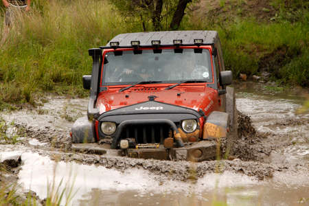 the jeep: BAFOKENG - MARCH 8 Crush Orange Jeep Rubicon crossing muddy pond obstacle at Leroleng 4x4 track on March 8, 2014 in Bafokeng, Rustenburg, South Africa
