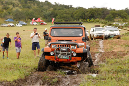 rustenburg: BAFOKENG - MARCH 8: Crush Beige Jeep Wrangler Off-Roader V8 crossing water obstacle at Leroleng 4x4 track on March 8, 2014 in Bafokeng, Rustenburg, South Africa Editorial