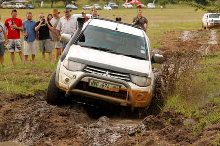 rustenburg: BAFOKENG - MARCH 8: White Toyota Triton DHD crossing mud obstacle at Leroleng 4x4 track on March 8, 2014 in Bafokeng, Rustenburg, South Africa