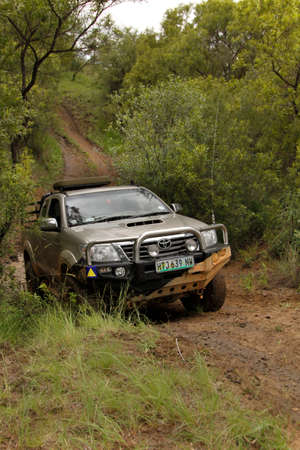 raider: BAFOKENG - MARCH 8: White Toyota Raider Hilux 3.0L crossing obstacle at Leroleng 4x4 track on March 8, 2014 in Bafokeng, Rustenburg, South Africa