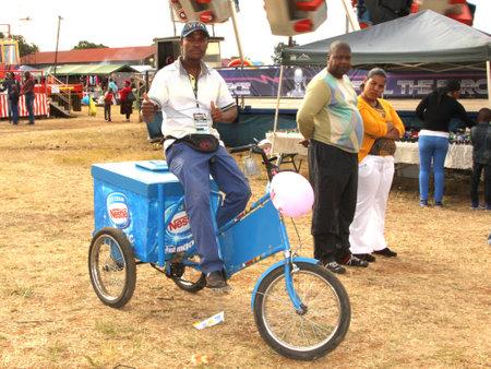 rustenburg: RUSTENBURG, SOUTH AFRICA - MAY 25: Black African Ice-cream Salesman at Rustenburg Fair on May 25, 2014 in Rustenburg South Africa.