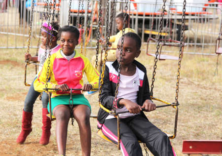 rustenburg: RUSTENBURG, SOUTH AFRICA - MAY 25: Black African children waiting for roundabout ride to start at Rustenburg Fair on May 25, 2014 in Rustenburg South Africa.