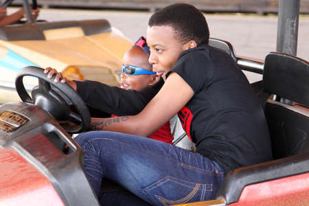 rustenburg: RUSTENBURG, SOUTH AFRICA - MAY 25: Black African brother and sister enjoying bumper cars at Rustenburg Fair on May 25, 2014 in Rustenburg South Africa.