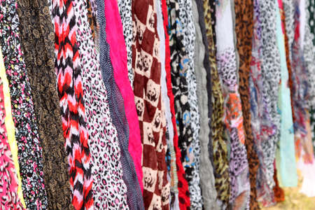 scarves: Variety of Hanging Scarves Providing Colourful Backdrop for Graphic Artists Stock Photo