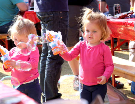 captivated: THABAZIMBI, SOUTH AFRICA - JUNE 28: Two Small Sisters Playing with Bubble Makers at Wildsfees (Game Festival) on June 28, 2014 in Thabazimbi South Africa.