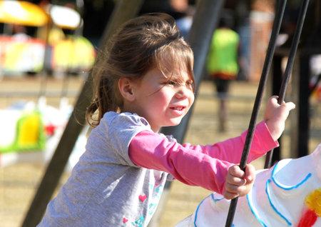 joyride: THABAZIMBI, SOUTH AFRICA - JUNE 28: Sweet little girl riding on carousel  at Wildsfees (Game Festival) on June 28, 2014 in Thabazimbi South Africa.