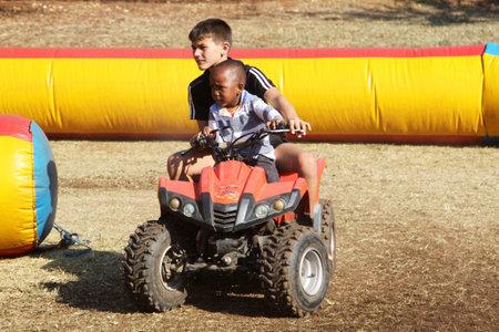 joyride: THABAZIMBI, SOUTH AFRICA - JUNE 28: White boy helping Black boy riding on quad bike at Wildsfees (Game Festival) on June 28, 2014 in Thabazimbi South Africa.