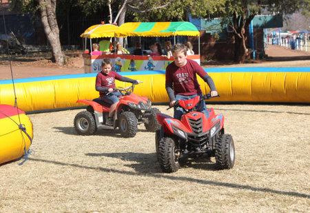 joyride: THABAZIMBI, SOUTH AFRICA - JUNE 28: Boys riding on quad bikes at Wildsfees (Game Festival) on June 28, 2014 in Thabazimbi South Africa. Editorial