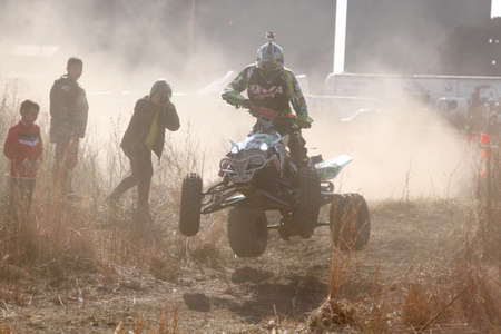 BRITS, SOUTH AFRICA - July 11:  Africa-Offroad Racing Rally,  on July 11, 2015 at Koster, North West Province, South Africa.  Quad Bike airborne over hump in trail of dust on sand track during rally race. Editorial