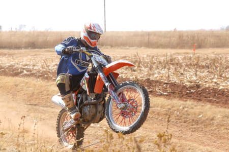 scrambler: BRITS, SOUTH AFRICA - July 11:  Africa-Offroad Racing Rally,  on July 11, 2015 at Koster, North West Province, South Africa.  Motorbike wheelie on back wheel kicking up trail of dust on sand track during rally race.