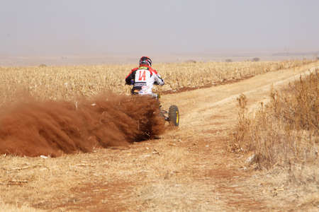 powerfull: BRITS, SOUTH AFRICA - July 11:  Africa-Offroad Racing Rally,  on July 11, 2015 at Koster, North West Province, South Africa.  Quad Bike kicking up trail of dust on sand track during rally race.