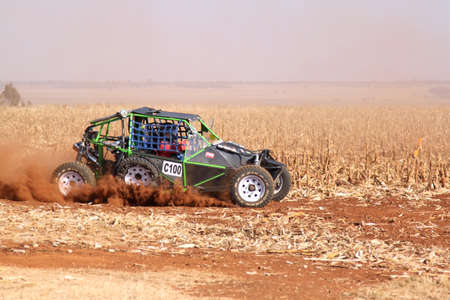seater: BRITS, SOUTH AFRICA - July 11:  Africa-Offroad Racing Rally,  on July 11, 2015 at Koster, North West Province, South Africa.  Custom single seater rally buggy kicking up trail of dust on sand track during rally race.