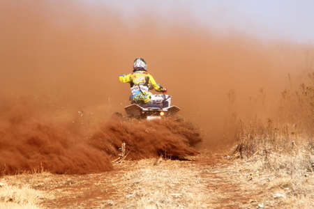quad: BRITS, SOUTH AFRICA - July 11:  Africa-Offroad Racing Rally,  on July 11, 2015 at Koster, North West Province, South Africa.  Quad Bike kicking up trail of dust on sand track during rally race.