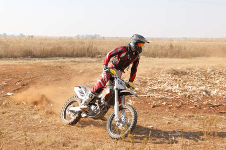scrambler: BRITS, SOUTH AFRICA - July 11:  Africa-Offroad Racing Rally,  on July 11, 2015 at Koster, North West Province, South Africa.  Motorbike kicking up trail of dust on sand track during rally race.