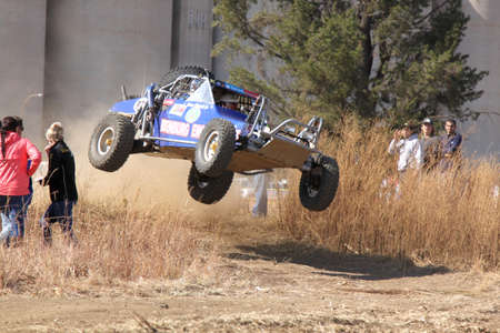 BRITS, SOUTH AFRICA - July 11:  Africa-Offroad Racing Rally,  on July 11, 2015 at Koster, North West Province, South Africa.  Custom twin seater rally buggy airborne over bump on sand track during rally race.