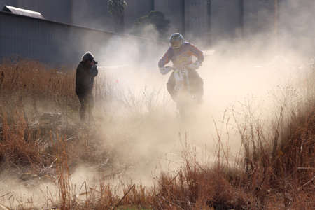 BRITS, SOUTH AFRICA - July 11:  Africa-Offroad Racing Rally,  on July 11, 2015 at Koster, North West Province, South Africa.  Motorbike airborne over bump in dust on sand track during rally race.