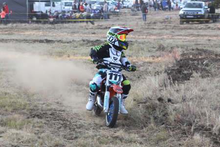 scrambler: BRITS, SOUTH AFRICA - July 11:  Africa-Offroad Racing Rally,  on July 11, 2015 at Koster, North West Province, South Africa.  Kiddy motorbike rider speeding down track on mini motorbike. Editorial