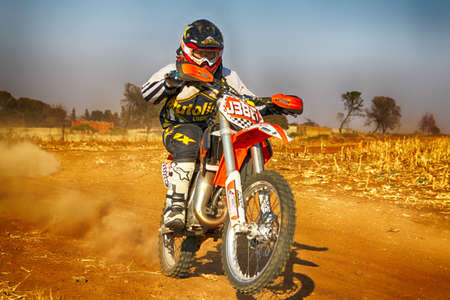 scrambler: KOSTER, SOUTH AFRICA - July 11:  Africa-Offroad Racing Rally,  on July 11, 2015 at Koster, North West Province, South Africa.  HD - Junior Motorbike kicking up trail of dust on sand track during rally race. Editorial