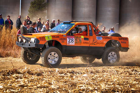 south africa soil: KOSTER, SOUTH AFRICA - July 11:  Africa-Offroad Racing Rally,  on July 11, 2015 at Koster, North West Province, South Africa.  HD orange truck kicking up dust on turn at rally. Editorial