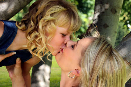 Mom and daughter Loving Kiss from Tree