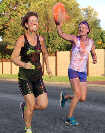 rustenburg: Rustenburg Marathon Club Rainbow Run - NOVEMBER 25: Young lady plashing other with orange powder paint at colour run on November 25, 2015, Rustenburg, South Africa.