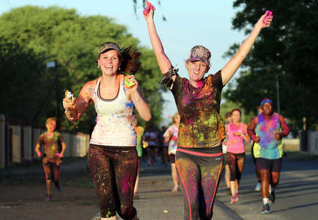 rustenburg: Rustenburg Marathon Club Rainbow Run - NOVEMBER 25: Chearful running young girls covered with powder paint at colour run on November 25, 2015, Rustenburg, South Africa.